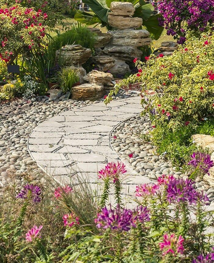 Trockenmauer aus Grauwackesteinen, im Beet wachsen vorn Sedum, Wollziest, Polster-Phlox, dahinter Segge, Heuchera und Hortensien